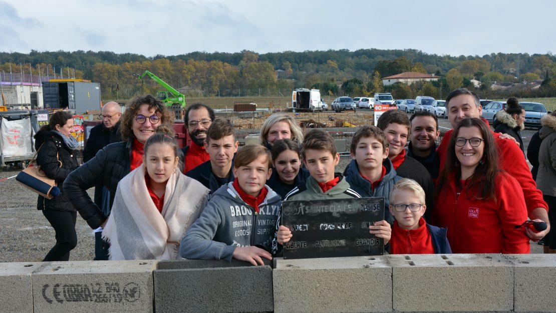 Les jeunes posent devant la 1ère pierre de leur futur collège